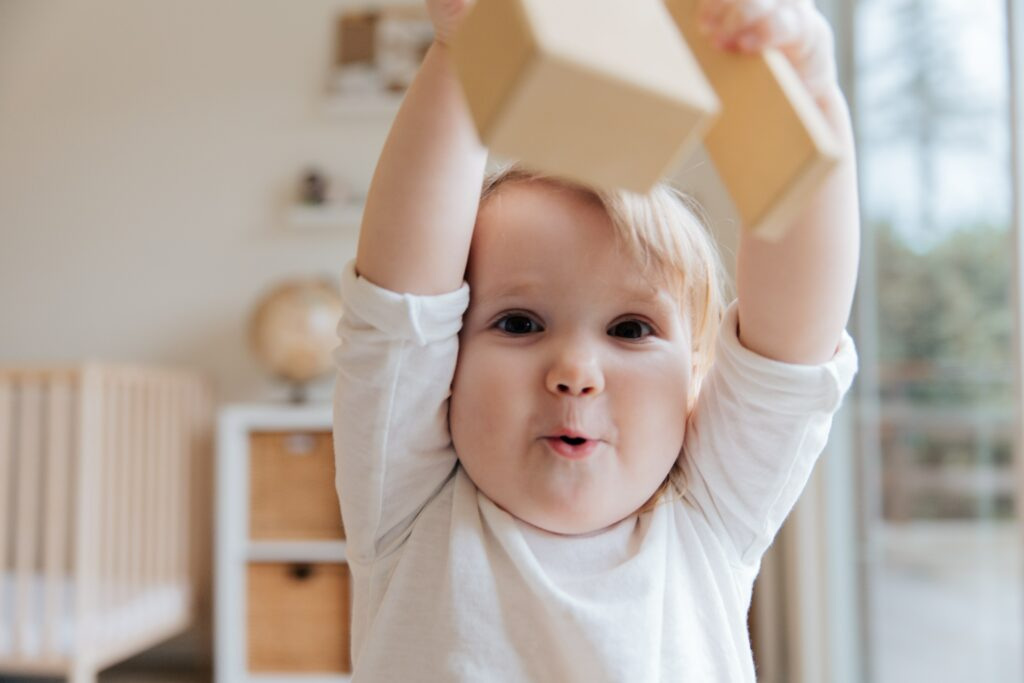 Baby in white onesie playing with wooden blocks.